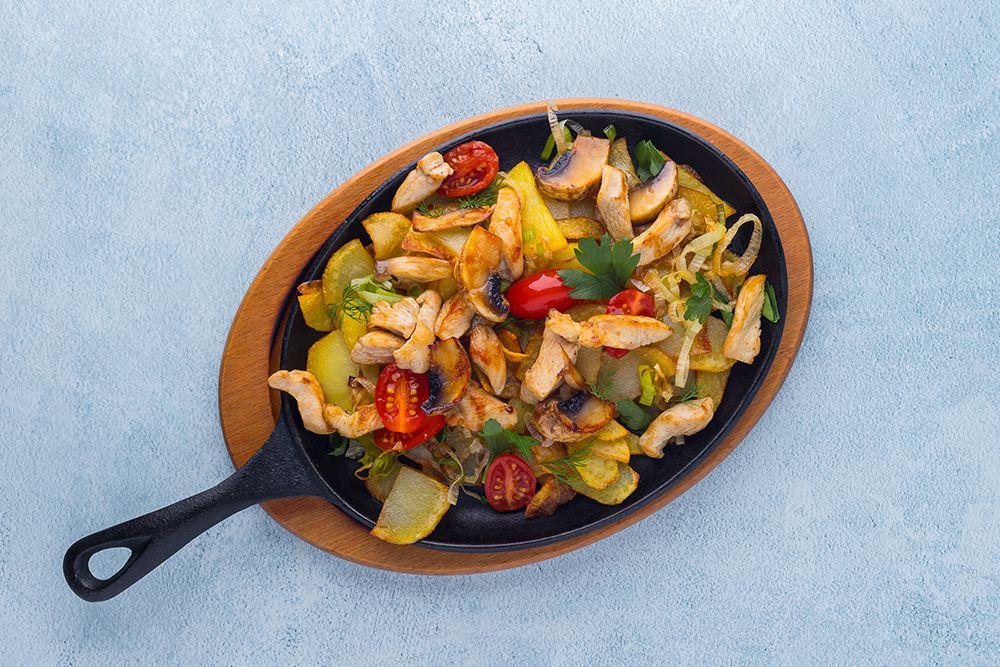 Мясная сковородка с картофелем, грибами, помидором и курицей