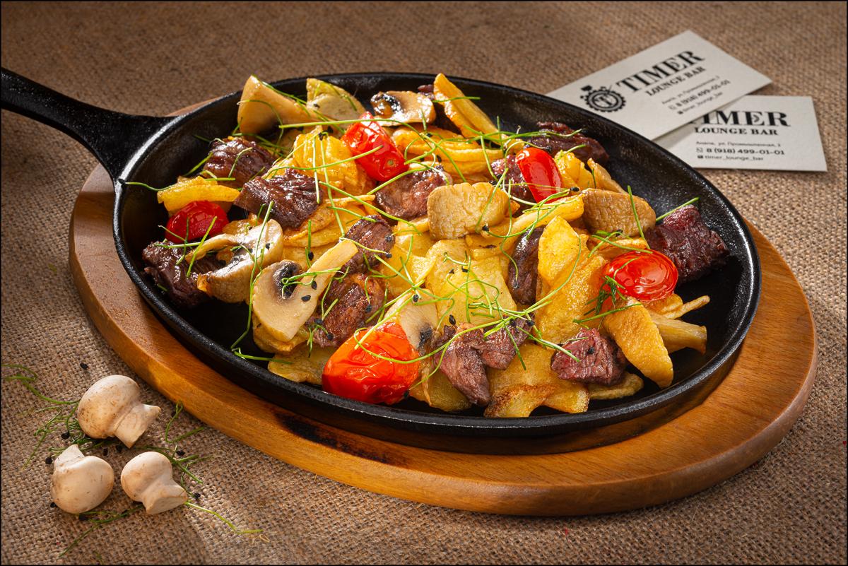 Мясная сковородка с картофелем, грибами, помидором и говядиной