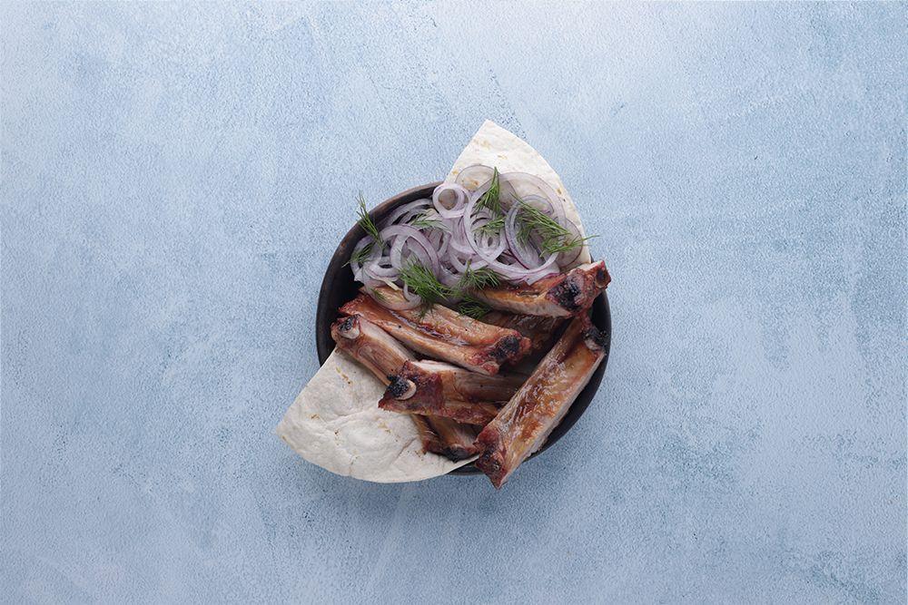 Свиные ребра на лаваше с маринованным луком и зеленью.